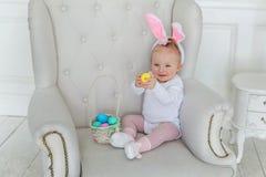 Muchacha en los oídos de un conejo con una cesta de huevos imagen de archivo libre de regalías