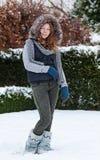 Muchacha en los paños del invierno que se colocan en nieve Fotos de archivo