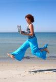 Muchacha en los pantalones azules que se ejecutan con la computadora portátil Imagen de archivo libre de regalías