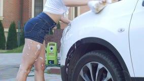 Muchacha en los pantalones cortos para lavar el coche almacen de metraje de vídeo
