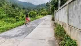 Muchacha en los pantalones cortos rojos que montan la bicicleta fotos de archivo libres de regalías