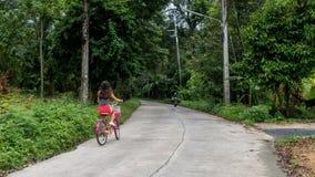 Muchacha en los pantalones cortos rojos que montan la bicicleta foto de archivo