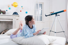 Muchacha en los pijamas que mienten en cama con la tableta digital y que miran el telescopio imagenes de archivo