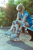 Muchacha en los rollerblades que se sientan en un banco en un parque y que ponen en patines en línea en una luz brillante soleada Imagen de archivo libre de regalías