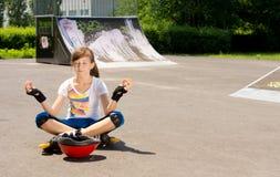 Muchacha en los rollerblades que sientan meditar Fotografía de archivo libre de regalías