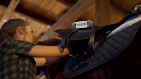 Muchacha en los sistemas estables la silla de montar en el caballo almacen de metraje de vídeo