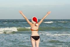 Muchacha en los sombreros de Papá Noel con el Año Nuevo de la inscripción en la parte posterior Orilla de mar Manos levantadas pa Foto de archivo libre de regalías