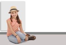 Muchacha en los vaqueros, las botas, el sombrero y la camiseta sentándose en el piso Imagenes de archivo