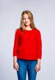 Muchacha en los vaqueros y el suéter rojo, mujer, tiro del estudio Imagenes de archivo