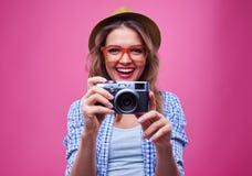 Muchacha en los vidrios anaranjados que toman la foto con una cámara retra de plata Fotografía de archivo libre de regalías