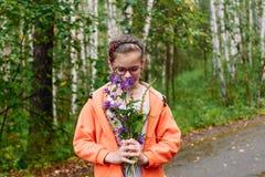 Muchacha en los vidrios que huelen wildflowers fotografía de archivo