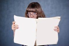 Muchacha en los vidrios que miran sobre el periódico Imagenes de archivo
