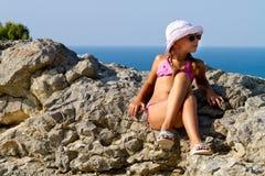 Muchacha en los vidrios que se sientan en las rocas por el mar Fotos de archivo