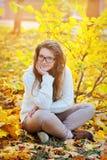 Muchacha en los vidrios que se sientan en parque del otoño en las hojas Fotos de archivo