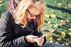 Muchacha en los vidrios que se sientan en parque y que usan smartphone Imagenes de archivo