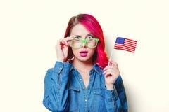 Muchacha en los vidrios verdes que sostienen la bandera de Estados Unidos Foto de archivo