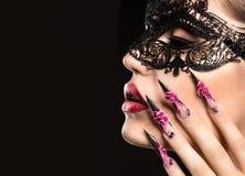 Muchacha en máscara con los clavos largos y sensual hermosos Imagen de archivo libre de regalías