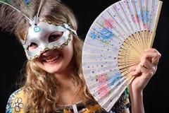 Muchacha en máscara con un ventilador Imagen de archivo