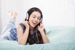 Muchacha en música que escucha de los auriculares Fotos de archivo libres de regalías