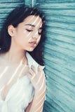 Muchacha en magro tranquilo de la cara en persiana de la turquesa Morenita de la mujer que se enfría mientras que soportes cerca  foto de archivo libre de regalías