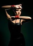 Muchacha en manillas rojas Foto de archivo libre de regalías