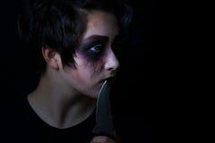 Muchacha en maquillaje asustadizo con el cuchillo del combate en fondo negro Foto de archivo