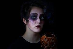 Muchacha en maquillaje asustadizo con el envase de la calabaza en fondo negro Imagen de archivo libre de regalías