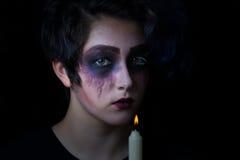 Muchacha en maquillaje asustadizo con la vela de lite en fondo negro Foto de archivo libre de regalías