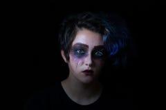 Muchacha en maquillaje asustadizo en fondo negro Fotos de archivo