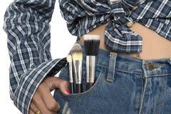 Muchacha en mezclilla azul con los cepillos del maquillaje en bolsillo delantero imagenes de archivo