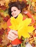 Muchacha en naranja en follaje del otoño con la hoja amarilla. Fotos de archivo libres de regalías