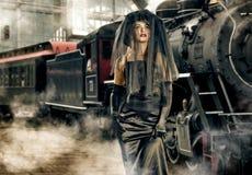 Muchacha en negro y locomotora Fotos de archivo