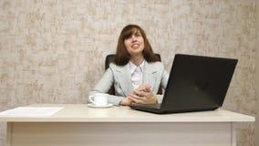 Muchacha en oficina en el funcionamiento de la mesa en el ordenador y hablar El empresario de sexo femenino joven comunica con el imagenes de archivo