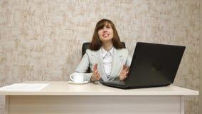 Muchacha en oficina en el funcionamiento de la mesa en el ordenador y hablar El empresario de sexo femenino joven comunica con el fotografía de archivo