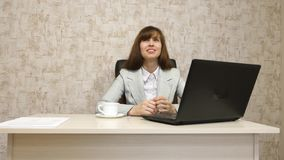 Muchacha en oficina en el funcionamiento de la mesa en el ordenador y hablar El empresario de sexo femenino joven comunica con el fotos de archivo libres de regalías