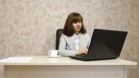 Muchacha en oficina en el funcionamiento de la mesa en el ordenador y hablar El empresario de sexo femenino joven comunica con el fotografía de archivo libre de regalías