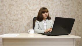 Muchacha en oficina en el funcionamiento de la mesa en el ordenador y hablar El empresario de sexo femenino joven comunica con el foto de archivo libre de regalías