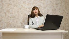 Muchacha en oficina en el funcionamiento de la mesa en el ordenador y hablar El empresario de sexo femenino joven comunica con el imágenes de archivo libres de regalías