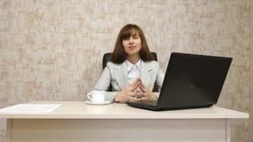 Muchacha en oficina en el funcionamiento de la mesa en el ordenador y hablar El empresario de sexo femenino joven comunica con el metrajes