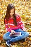 Muchacha en otoño con la tableta Imagen de archivo libre de regalías