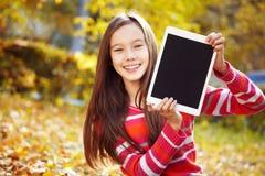 Muchacha en otoño con la tableta Foto de archivo libre de regalías