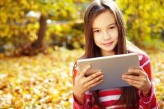 Muchacha en otoño con la tableta Foto de archivo