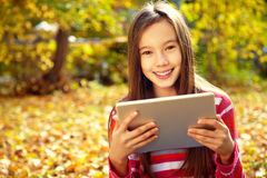 Muchacha en otoño con la tableta Imagenes de archivo
