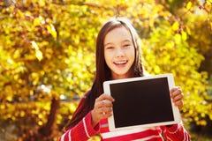 Muchacha en otoño con la tableta Imágenes de archivo libres de regalías