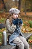 Muchacha en paños del invierno que bebe de la taza del frasco Fotos de archivo