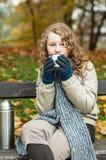 Muchacha en paños del invierno que bebe de la taza del frasco Imágenes de archivo libres de regalías