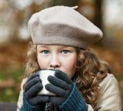 Muchacha en paños del invierno que bebe de la taza del frasco Imagen de archivo