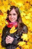 Muchacha en paisaje colorido de las hojas del otoño Foto de archivo