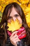 Muchacha en paisaje colorido de las hojas del otoño Imagenes de archivo