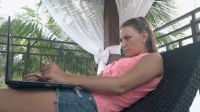 Muchacha en pantalones cortos de los vaqueros y tipos de la blusa en el cuaderno en terraza almacen de video
